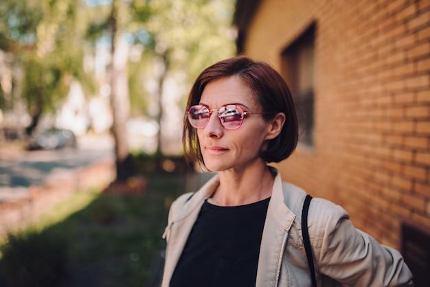 Porträt der tragenden sonnenbrille der jungen frau