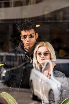Porträt der tragenden sonnenbrille der zwischen verschiedenen rassen stilvollen jungen paare, die kamera betrachtet