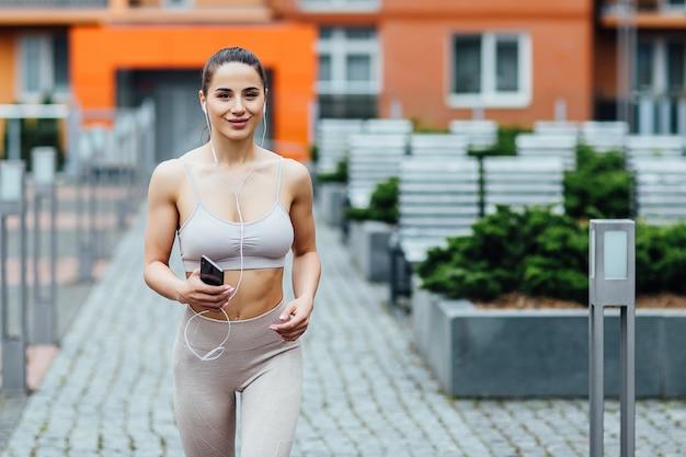 Porträt der tragenden sportkurzschlüsse der starken athletischen glücklichen sportlerin, die sprung nahe haus vorbereiten.