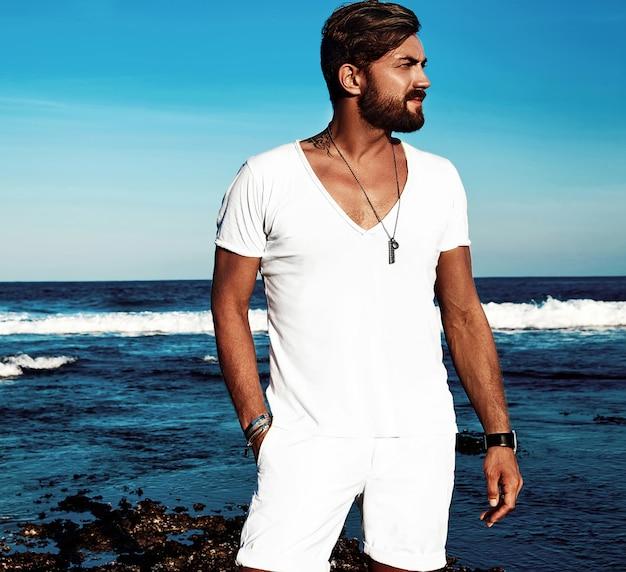 Porträt der tragenden weißen kleidung des hübschen modemannmodells, die auf blauem meer aufwirft