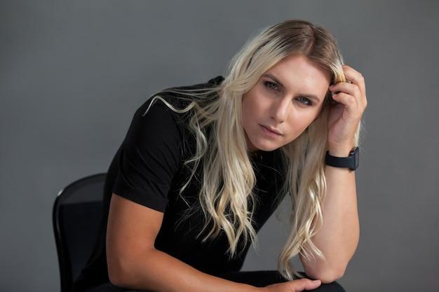 Porträt der transgenderfrau, die auf stuhl sitzt