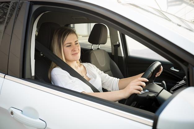Porträt der traurigen blonden frau, die auto fährt