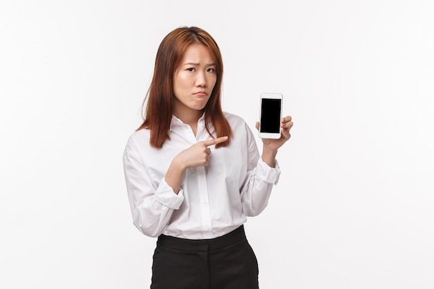 Porträt der traurigen düsteren asiatischen frau fühlen sich unwohl und verärgert, handy-display haltend, finger auf smartphone zeigend und unglücklichen verzweifelten ausdruck zu machen,