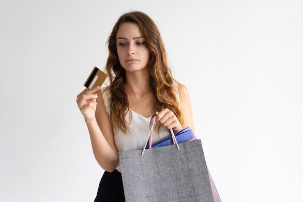 Porträt der traurigen frau mit den einkaufstaschen, die kreditkarte betrachten.
