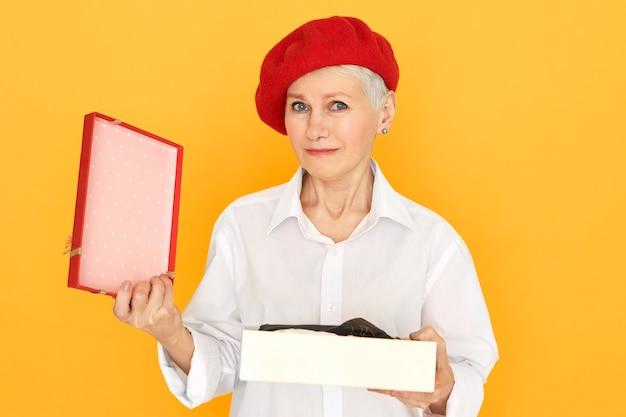 Porträt der traurigen frustrierten reifen pensionierten frau in der roten baskenmützen-haltebox, geschenk am valentinstag auspackend