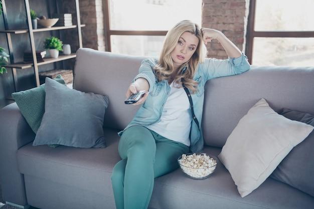 Porträt der traurigen gelangweilten welligen dame, die auf diwan sitzt, der popcorn isst, das fernsehen sieht