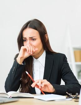 Porträt der traurigen jungen geschäftsfrau, die roten bleistift in ihrem handschreien hält