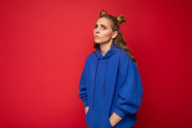 Porträt der traurigen müden jungen attraktiven gewinnenden blonden frau mit zwei hörnern mit aufrichtigen gefühlen, die lässigen hellblauen hoodie tragen, der auf roter oberfläche mit freiem raum isoliert wird