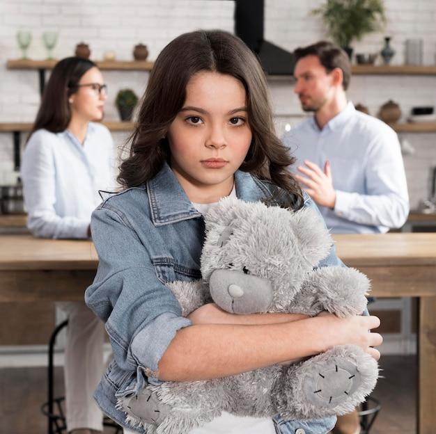 Porträt der traurigen tochter, die teddybär hält