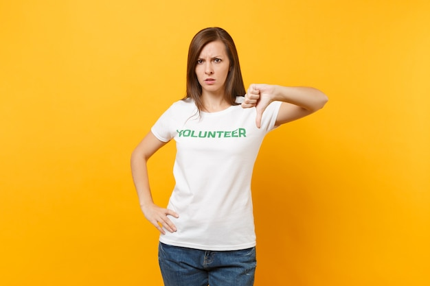 Porträt der traurigen verärgerten schockierten jungen frau im weißen t-shirt mit der schriftlichen aufschrift grüner titelfreiwilliger lokalisiert auf gelbem hintergrund. freiwillige kostenlose hilfe, konzept der wohltätigkeitsarbeit.