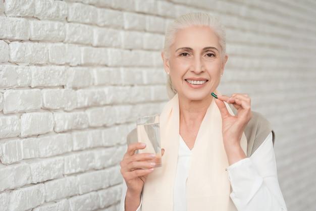 Porträt der trinkenden pille der reifen frau mit wasser.
