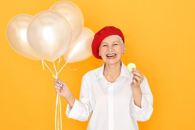 Porträt der überglücklichen ekstatischen europäischen frau mittleren alters, die weiße bluse und rote baskenmütze lachend trägt