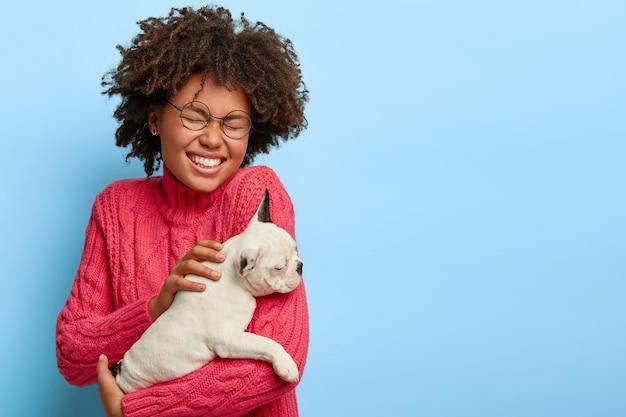 Porträt der überglücklichen hündin hält kleinen weißen welpen, lacht positiv, ist gut gelaunt nach einem spaziergang im freien mit lieblingshaustier, gekleidet in casaul-pullover, hat afro-haare. tierkonzept
