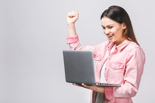 Porträt der überraschten aufgeregten lächelnden hand halten, die laptop-bildschirm betrachtet, lokalisiert über weißem hintergrund,