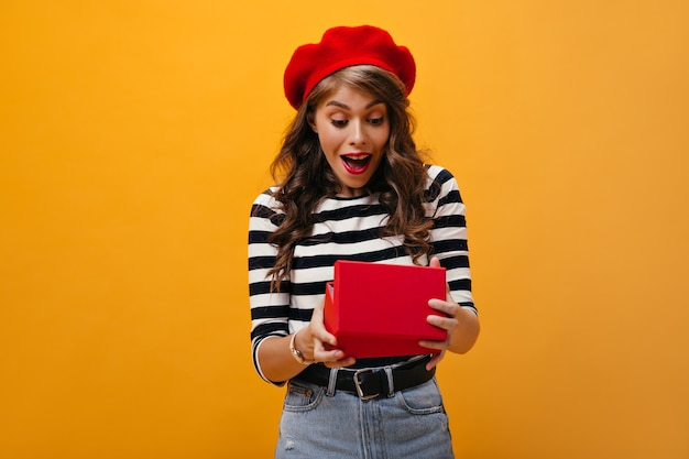 Porträt der überraschten frau im gestreiften hemd auf orange hintergrund. modisches süßes mädchen mit lockigem haar im trendigen outfit, das aufwirft.