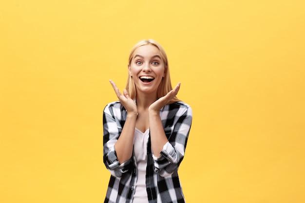 Porträt der überraschten jungen frau im weißen hemd, das vor gelber wand steht.
