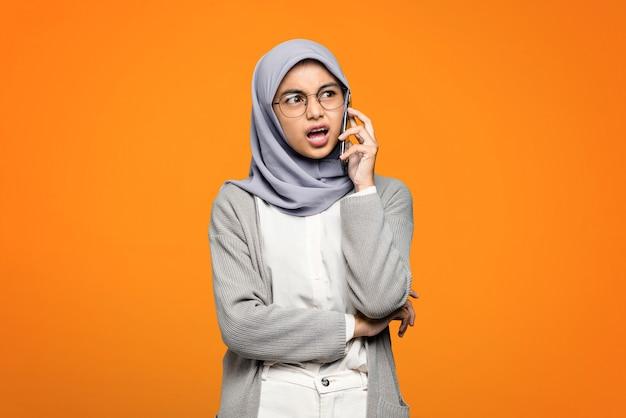 Porträt der überraschten schönen asiatischen frau beim sprechen mit freund am smartphone