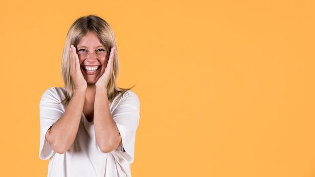 Porträt der überraschten tauben frau, die kamera über gelbem hintergrund betrachtet