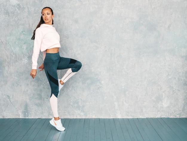 Porträt der überzeugten eignungsfrau in der sportkleidung, die überzeugt schaut das weibliche springen in studio nahe grauer wand