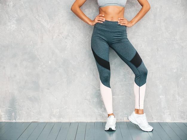 Porträt der überzeugten eignungsfrau in der sportkleidung, die überzeugt schaut frau, die im studio nahe grauer wand aufwirft