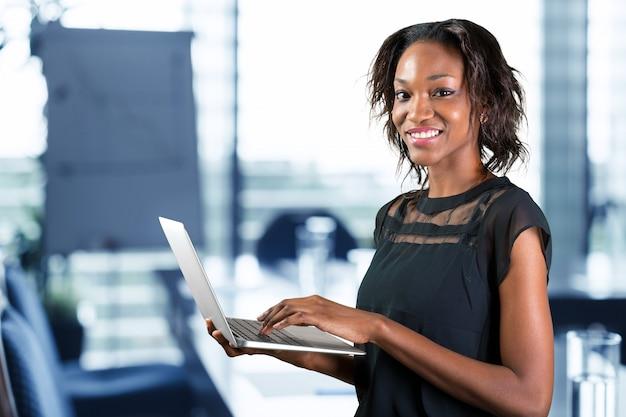 Porträt der überzeugten jungen afrikanischen frau, die laptop verwendet