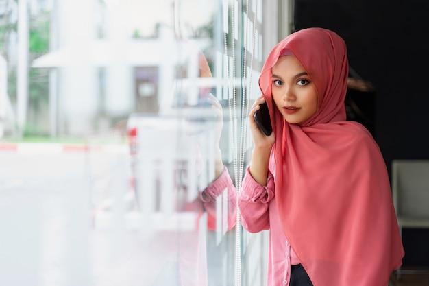 Porträt der überzeugten jungen moslemischen geschäftsfrau, die rosa hijab am mitarbeiterraum trägt.