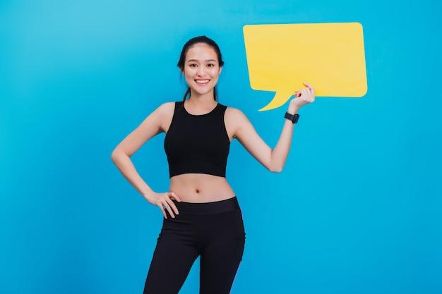Porträt der überzeugten schönen asiatischen eignungsfrau, die nach übung steht und leere gelbe blasenrede hält.