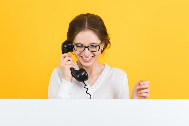 Porträt der überzeugten schönen aufgeregten lächelnden glücklichen jungen geschäftsfrau mit telefon