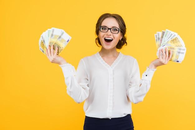 Porträt der überzeugten schönen glücklichen jungen geschäftsfrau mit geld in ihren händen, die auf gelbem hintergrund stehen