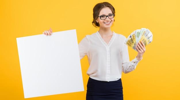 Porträt der überzeugten schönen jungen geschäftsfrau mit geld in ihren händen und in leerer anschlagtafel auf gelb