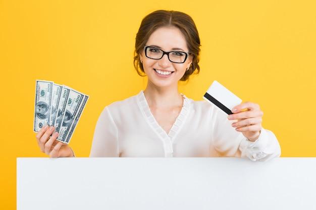 Porträt der überzeugten schönen jungen geschäftsfrau mit geld und kreditkarte in ihren händen mit leerer anschlagtafel auf gelb