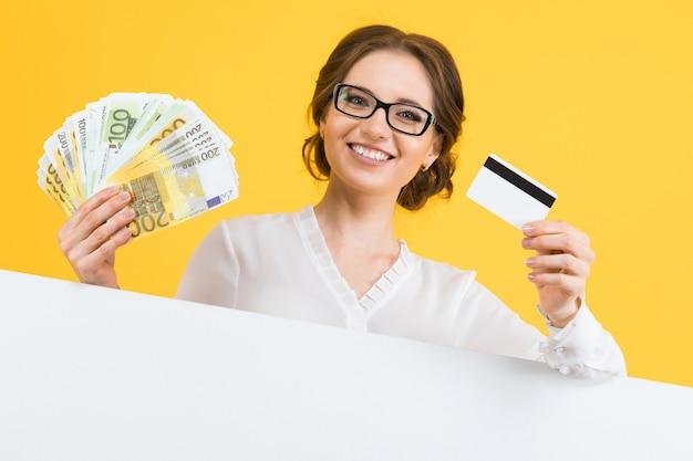 Porträt der überzeugten schönen jungen geschäftsfrau mit geld und kreditkarte in ihren händen