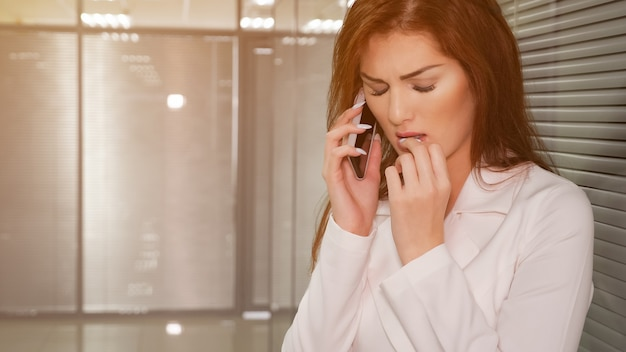 Porträt der unglücklichen jungen geschäftsfrau, die im büro am telefon spricht.