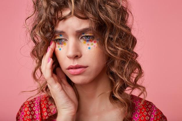 Porträt der unglücklichen jungen lockigen frau mit festlichem make-up, das sanft ihr gesicht berührt und mit leeren augen wegschaut und in farbig gemustertem oberteil aufwirft