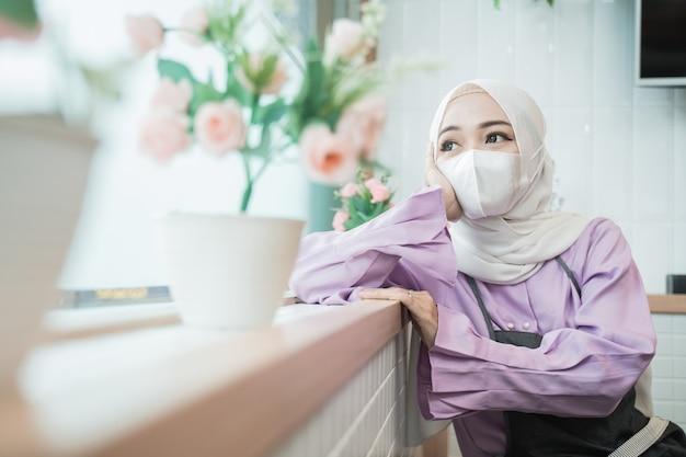 Porträt der unglücklichen jungen muslimischen frau tragen maske, während sie aus dem fenster schauen