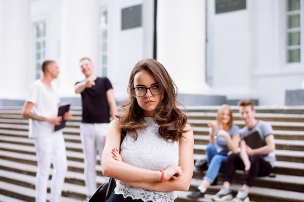 Porträt der unglücklichen und traurigen studentin beim einschüchtern von ihren gruppenmitgliedern. studenten, die streiche spielen, sich über ihren klassenkameraden an der treppe des colleges lustig machen.