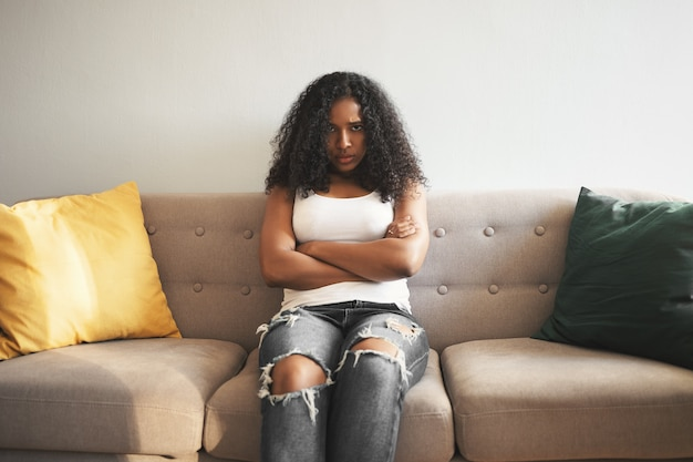 Porträt der unglücklichen wütenden jungen afroamerikanischen frau mit voluminösem haar, das auf sofa in geschlossener haltung sitzt, arme auf ihrer brust verschränkt, wütend auf ihren freund ist. negative menschliche emotionen