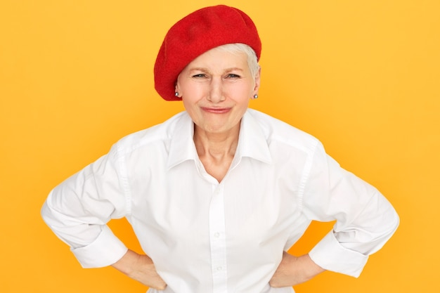 Porträt der unzufriedenen kurzhaarigen rentnerin, die elegante rote haube hält, die hände auf ihrer taille hält