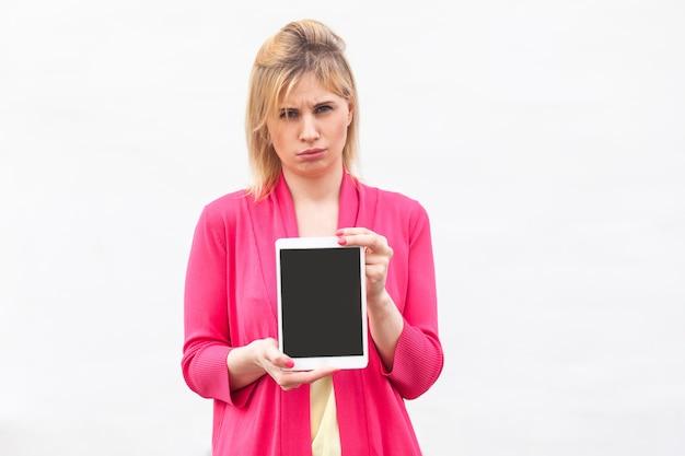 Porträt der unzufriedenen schönen jungen geschäftsfrau in der rosa bluse, die den leeren bildschirm der tablette steht und hält und die kamera mit unglücklichem gesicht betrachtet. innen, isoliert, studioaufnahme, weißer hintergrund