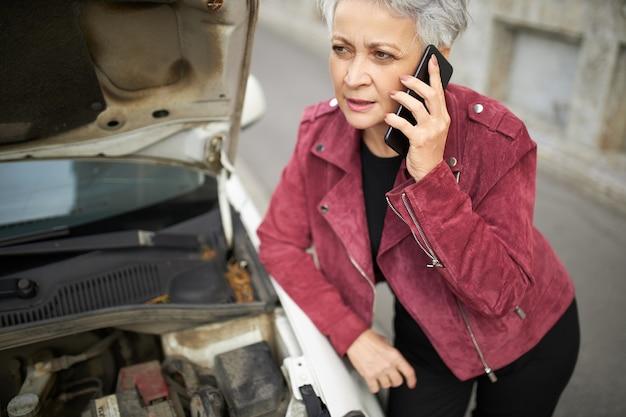 Porträt der verärgerten europäischen frau mittleren alters mit grauem kurzem haar, das an ihrem kaputten auto mit offener motorhaube wegen motorschaden steht