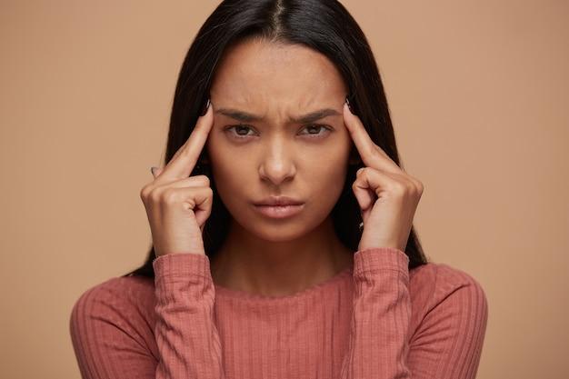 Porträt der verärgerten jungen asiatischen frau, die unter stress und kopfschmerzen leidet
