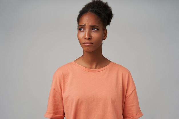Porträt der verärgerten jungen dunkelhäutigen lockigen dame mit brötchenfrisur, die die augenbrauen runzelt und die lippen gefaltet hält, während sie traurig beiseite schaut, isoliert auf grau