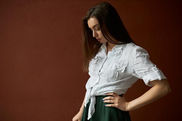Porträt der verärgerten modischen schönen jungen europäischen frau mit dem langen losen haar, das gegen leeren kopierraum-studiowandhintergrund aufwirft, der mit nachdenklichem traurigem gesichtsausdruck nach unten schaut