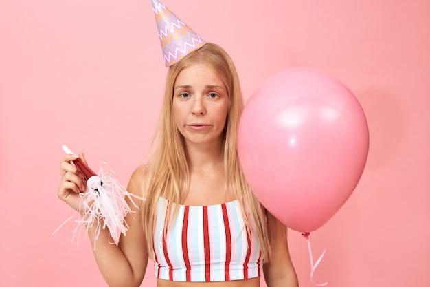 Porträt der verärgerten stilvollen jungen kaukasischen frau, die gestreiftes oberteil und konischen hut hält, der heliumballon hält, der gelangweilten gesichtsausdruck enttäuscht, der traurig und einsam ist