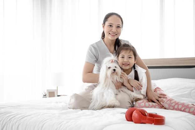 Porträt der verliebten familie mit braunem niedlichem hund entspannen und freizeit auf bett im schlafzimmer. sie haben haustiere als kameradschaft und lindern die einsamkeit.