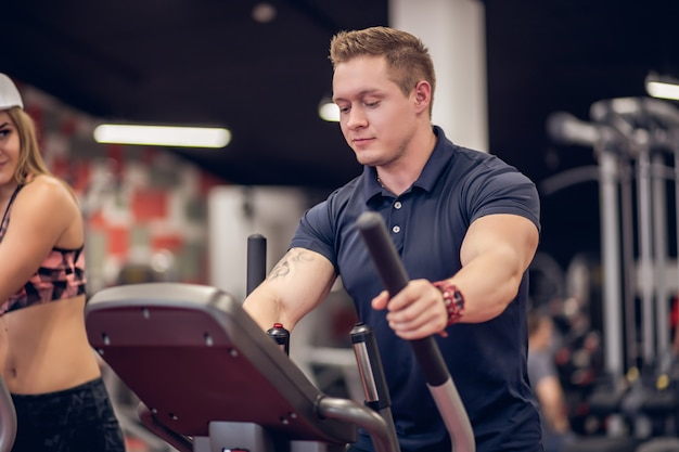 Porträt der verschwitzten fit frau, die mit ellipsentrainer während des intensiven trainings im modernen fitnessstudio trainiert