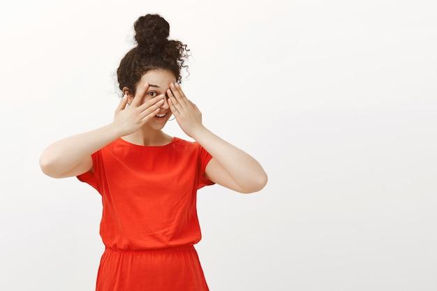 Porträt der verspielten glücklichen frau im niedlichen roten kleid mit dem im brötchen gekämmten lockigen haar