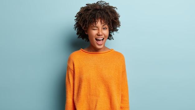 Porträt der verspielten lustigen jungen frau mit fröhlichem ausdruck, blinzelt auge, flirtet mit freund, drückt gute gefühle aus, trägt orangefarbenen pullover, isoliert über blauer wand.