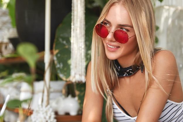 Porträt der verträumten entzückenden frau mit blondem haar leicht gebunden, trägt rote sonnenbrille