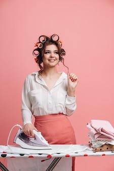 Porträt der verträumten hausfrau beim bügeln sauberer kleidung auf bügelbrett